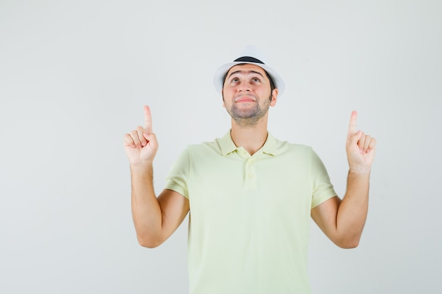 Junger mann, der in t-shirt, hut zeigt und hoffnungsvoll aussieht.