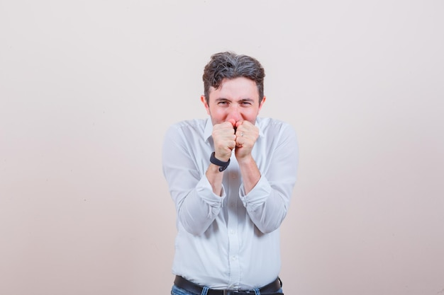 Junger mann, der in weißem hemd, jeans die fäuste über dem mund zusammenhält und glücklich aussieht