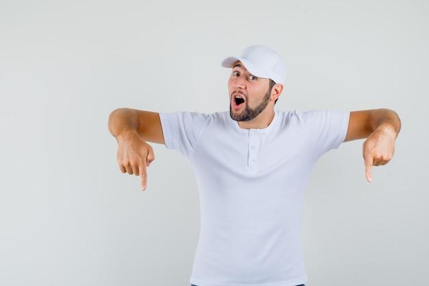 Junger mann, der in weißem t-shirt, mütze unten zeigt und energisch aussieht. vorderansicht.