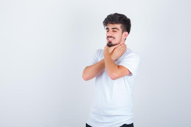 Junger mann, der in weißem t-shirt unter halsschmerzen leidet und krank aussieht