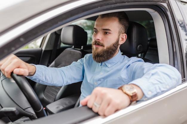 Junger mann, der innerhalb des autos sitzt