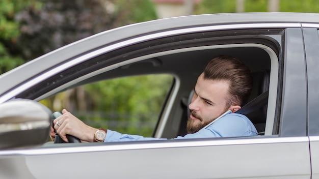 Junger mann, der innerhalb des autos spricht am handy sitzt