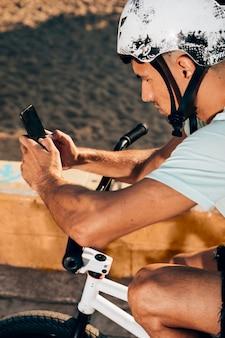 Junger mann, der intelligentes telefon auf seinem fahrrad verwendet