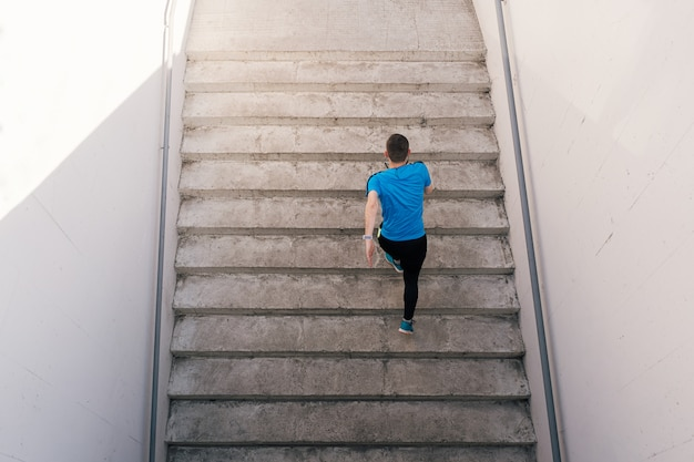 Junger mann, der intervalltraining auf treppen übt