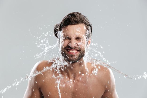 Junger mann, der isoliert über graue wand steht, wäscht gesicht