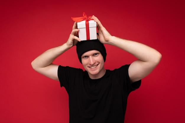 Junger mann, der isoliert über rotem hintergrund steht, der schwarzen hut und schwarzes t-shirt trägt, das weiße geschenkbox mit rotem band hält und kamera betrachtet.