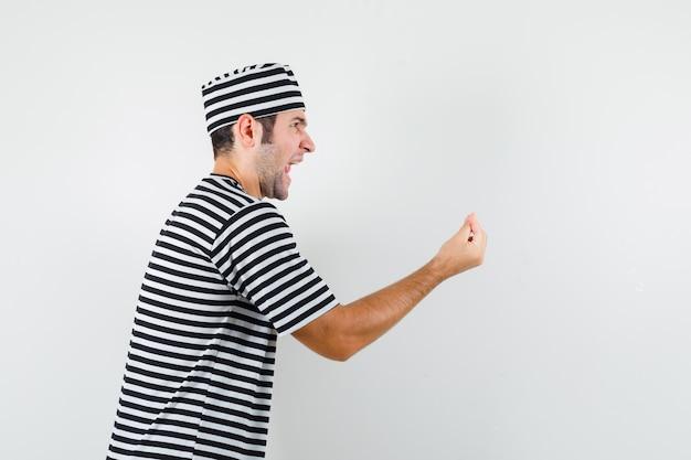 Junger mann, der italienische geste in t-shirt, hut tut und wütend schaut.