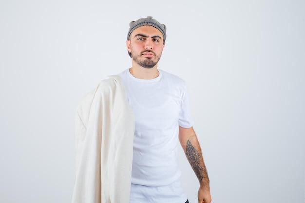 Junger mann, der jacke in weißem t-shirt, jacke und grauer mütze auf die schulter legt und ernst aussieht