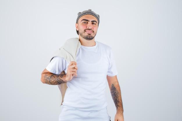 Junger mann, der jacke in weißem t-shirt, jacke und grauer mütze auf die schulter legt und glücklich aussieht