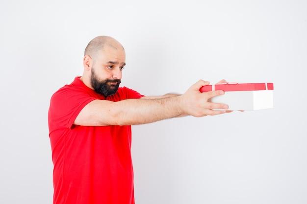 Junger mann, der jemandem im roten hemd eine geschenkbox gibt und traurig aussieht.
