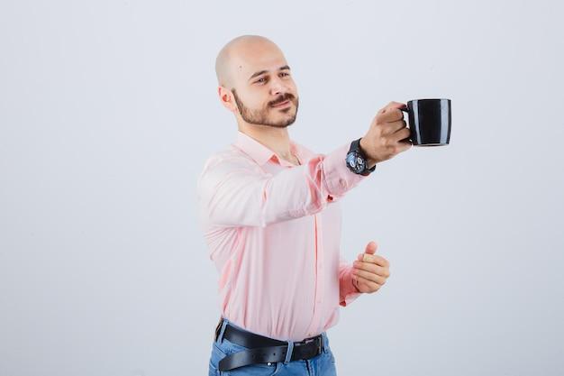 Junger mann, der jemandem in rosa hemd, jeans, vorderansicht tasse gibt.