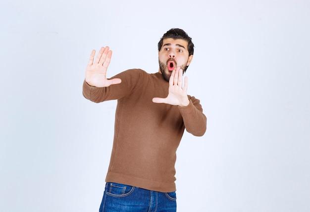 Junger mann, der jemanden ablehnt und eine geste des ekels zeigt.
