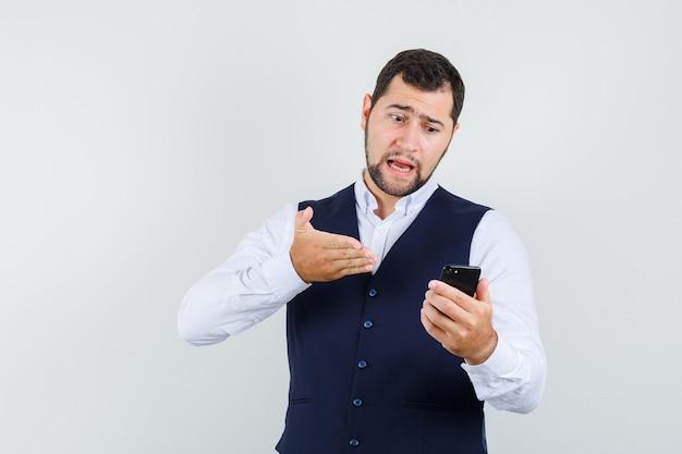 Junger mann, der jemanden verantwortlich auf video-chat im hemd, weste hält