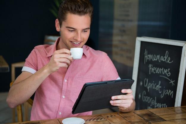 Junger mann, der kaffee beim verwenden der digitalen tablette im café verwendet