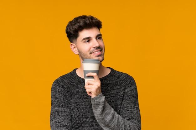 Junger mann, der kaffee hält, um wegzunehmen