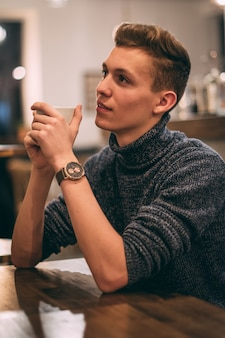 Junger mann, der kaffee im café trinkt