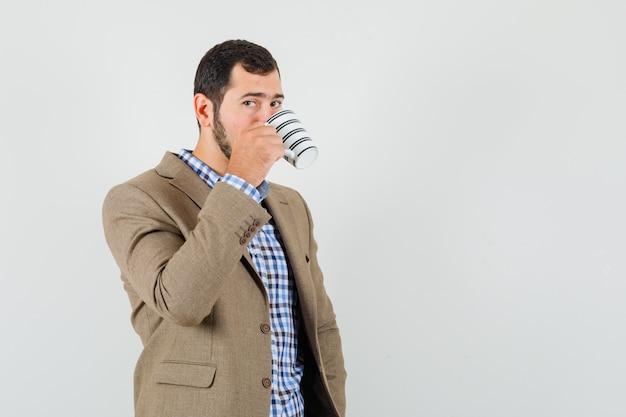 Junger mann, der kaffee im hemd, in der jacke trinkt und nachdenklich schaut. vorderansicht.