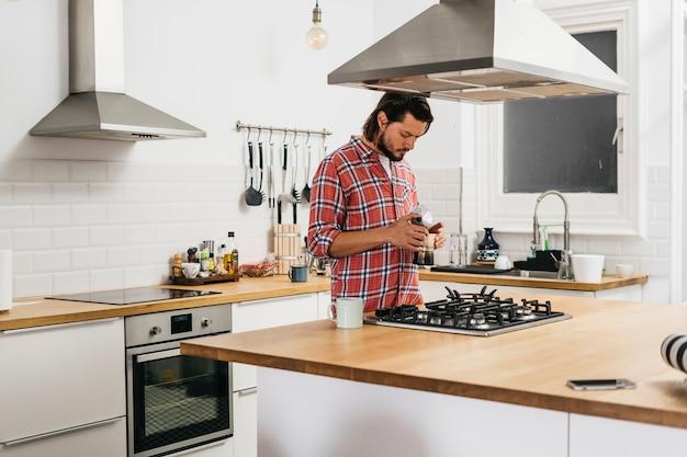 Junger mann, der kaffee in der modernen küche zubereitet