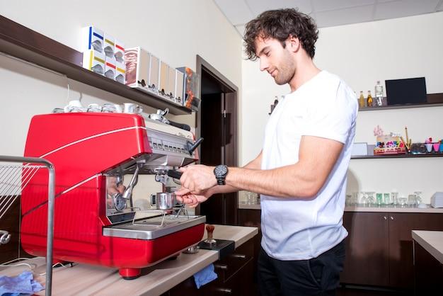 Junger mann, der kaffee macht