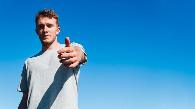 Junger mann, der kamera betrachtet und jemand gegen hintergrund des blauen himmels einlädt