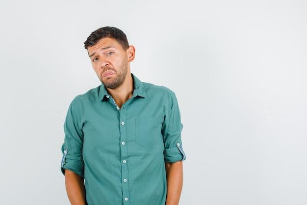 Junger mann, der kamera im hemd betrachtet und beleidigt schaut.