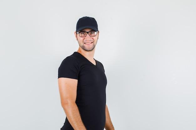 Junger mann, der kamera im schwarzen t-shirt betrachtet
