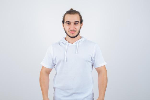 Junger mann, der kamera im t-shirt-kapuzenpulli betrachtet und selbstbewusst, vorderansicht schaut.