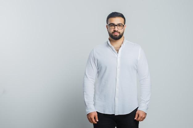 Junger mann, der kamera im weißen hemd, in den hosen betrachtet und gutaussehend schaut