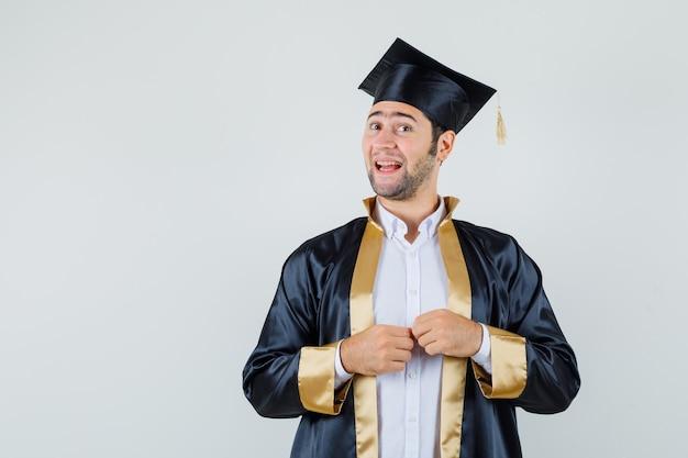 Junger mann, der kamera in der abschlussuniform betrachtet und fröhliche vorderansicht schaut.