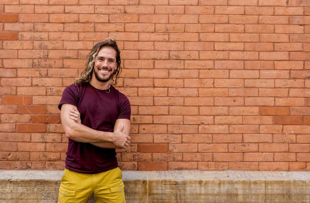 Junger mann, der kamera mit backsteinmauer betrachtet