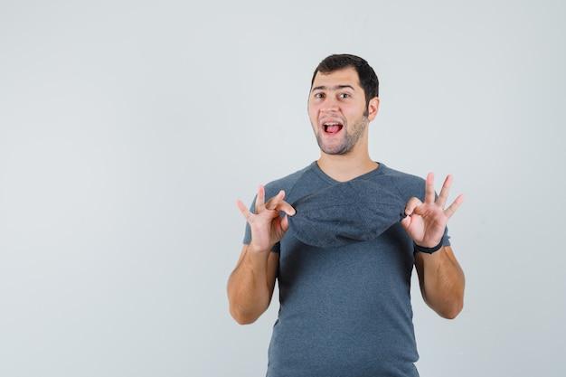 Junger mann, der kappe im grauen t-shirt hält und munter aussieht