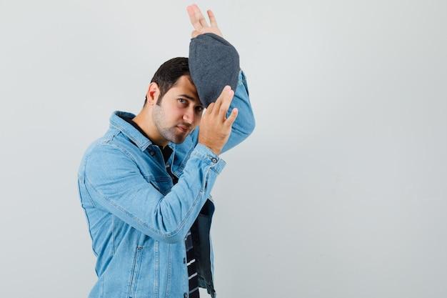 Junger mann, der kappe in jacke, t-shirt vorderansicht trägt. platz für text