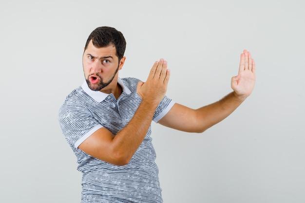 Junger mann, der karate-hieb-geste im t-shirt zeigt und mächtige vorderansicht schaut.