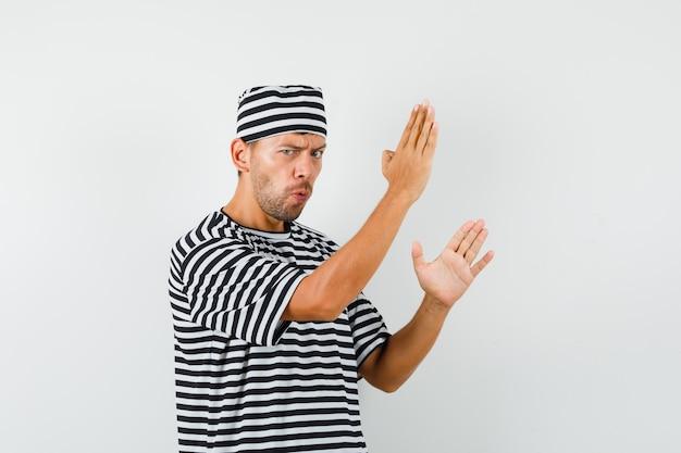 Junger mann, der karate-hiebgeste in gestreiftem t-shirt, hut zeigt und mächtig aussieht.