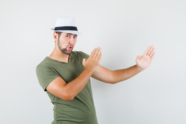 Junger mann, der karate-hiebgeste in grünem t-shirt und hut zeigt und stark schaut