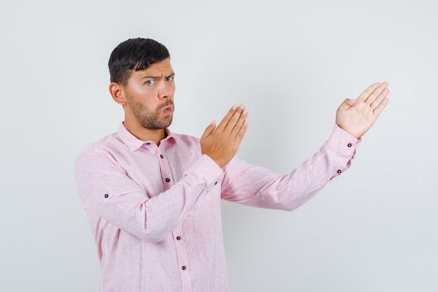 Junger mann, der karate-hiebgeste in rosa hemd zeigt und ernsthafte vorderansicht schaut.