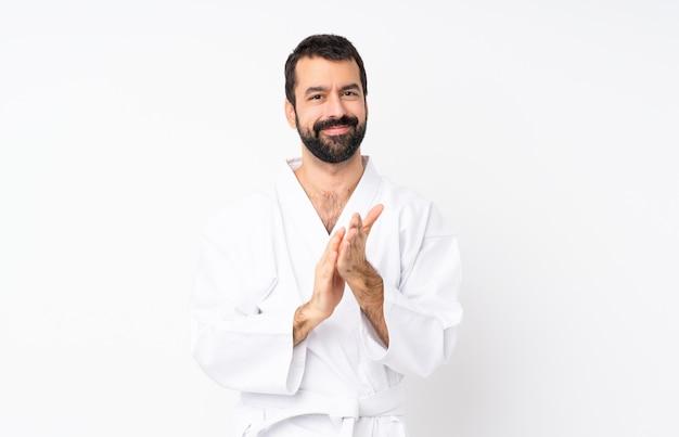 Junger mann, der karate über dem lokalisierten weiß applaudiert nach darstellung in einer konferenz tut