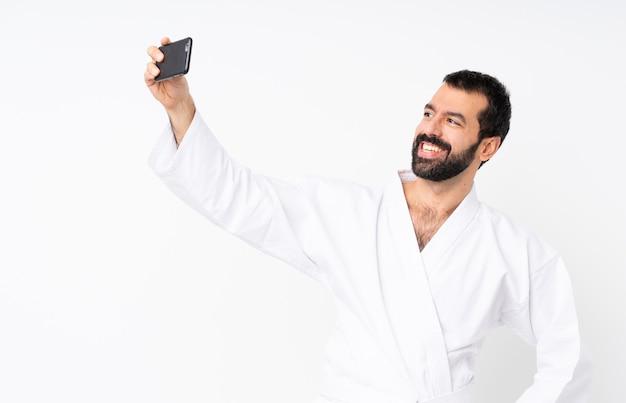 Junger mann, der karate über dem lokalisierten weiß macht ein selfie tut