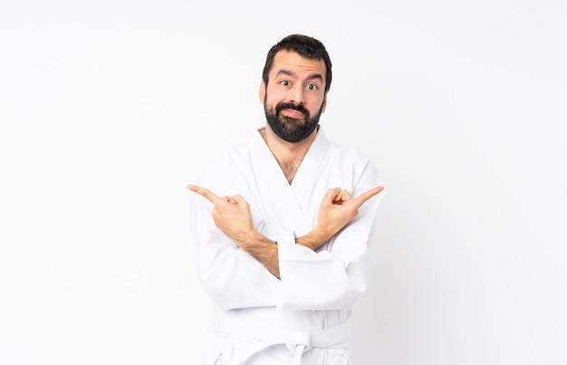 Junger mann, der karate über dem lokalisierten weiß zeigt auf die seitenteile hat zweifel tut