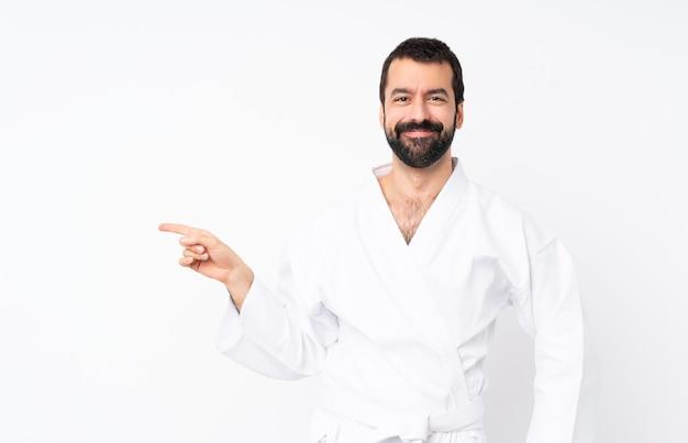 Junger mann, der karate über dem lokalisierten weißen hintergrund zeigt finger auf die seite tut