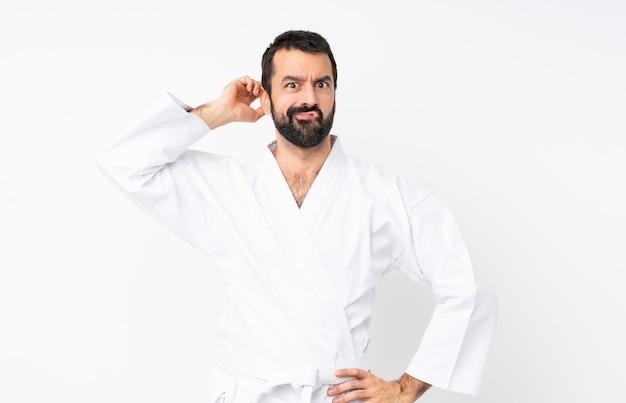 Junger mann, der karate über der lokalisierten weißen wand hat zweifel tut