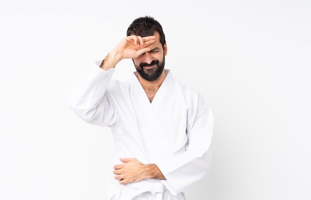 Junger mann, der karate über getrenntem weiß mit müdem und krankem ausdruck tut