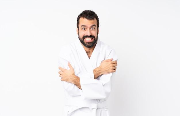 Junger mann, der karate über getrenntem weißem einfrieren tut