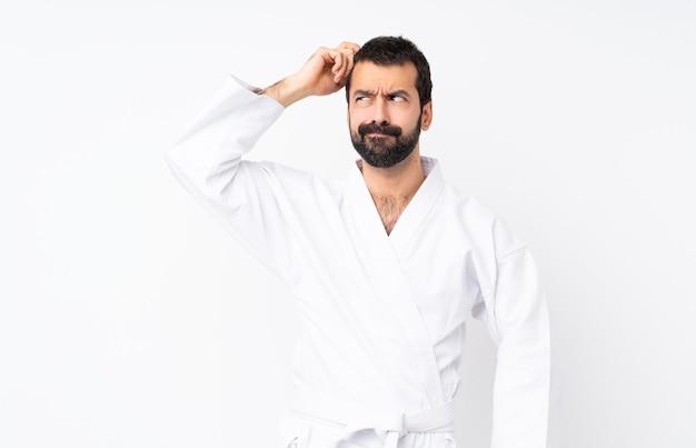 Junger mann, der karate über lokalisiertem haben von zweifeln beim verkratzen des kopfes tut