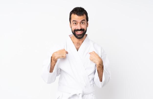 Junger mann, der karate über lokalisiertem weiß mit überraschungsgesichtsausdruck tut