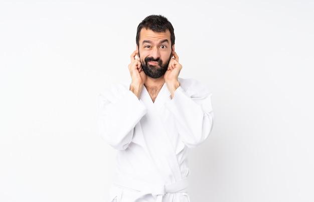 Junger mann, der karate über lokalisiertem weißem hintergrund frustriert tut und ohren bedeckt