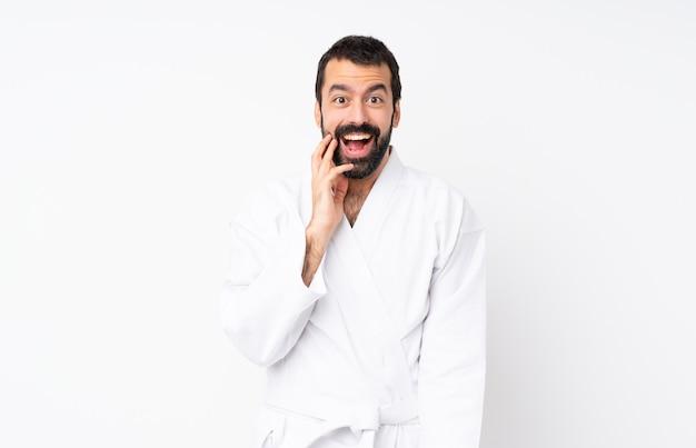 Junger mann, der karate über lokalisiertem weißem hintergrund mit überraschung und entsetztem gesichtsausdruck tut