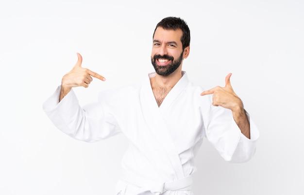 Junger mann, der karate über lokalisiertem weißem hintergrund stolz und selbstzufrieden tut