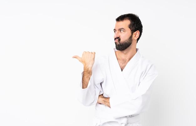 Junger mann, der karate über lokalisiertem weißem unglücklichem tut und auf die seite zeigt