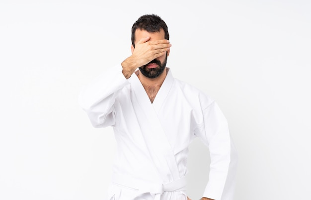 Junger mann, der karate über lokalisierter weißer bedeckung tut, mustert durch hände. ich will nichts sehen